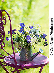 Garden idyll with flowers on a pink garden chair