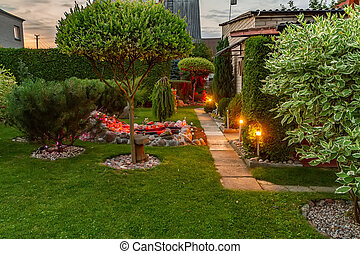 Garden illuminated by lamps in summer