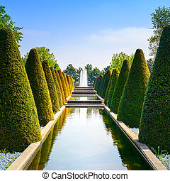 Garden in Keukenhof, conical hedges lines, water pool and fountain. Netherlands