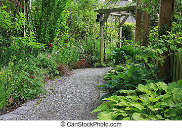 Garden path lined with hostas, grasses and other shade...