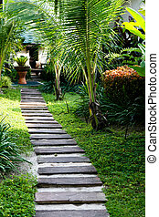 Lush tropical garden with a stone path.
