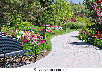 Brick pathway along a flower garden in a park with a bench.
