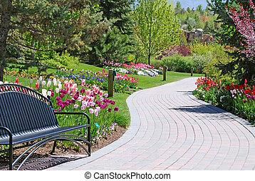 Garden Pathway - Brick pathway along a flower garden in a...