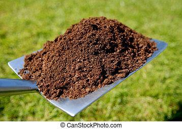 Garden spade with heap of organic compost.