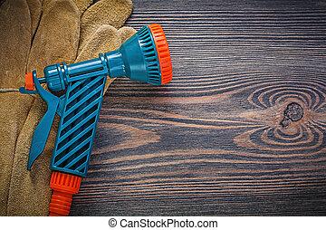 Garden spray nozzle protective gloves on vintage wood board gard