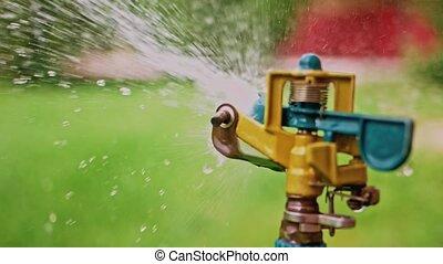 Garden sprinkler head spreading water in slomo
