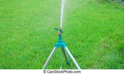 Garden sprinkler on tripod slow motion - Garden sprinkler on...