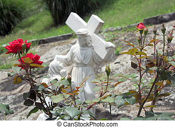 Garden Statue of Jesus - Red roses bloom in the garden of...