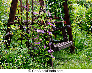 Garden swing. - Wooden bench in a flower garden.