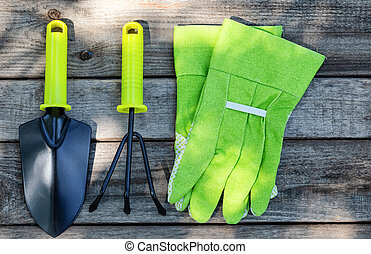 Garden tools and gloves on wooden background
