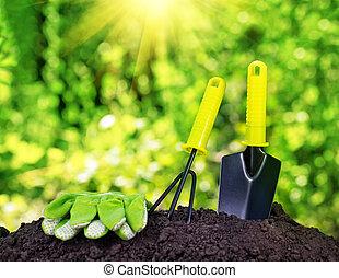 Garden tools rake trowel and gloves on pile of soil