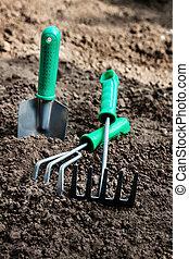 Garden tools, shovel, scoop, rake, villas lie on the soil, top view, close-up