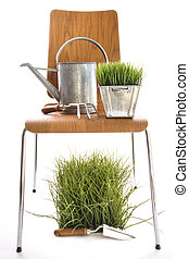 Garden tools, watering can on wood chair