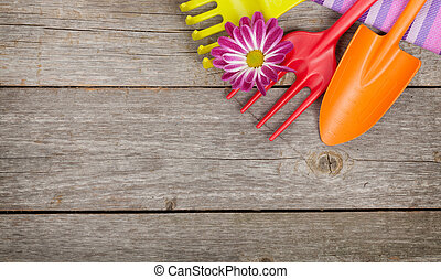 Garden tools with flower on wooden table background with ...