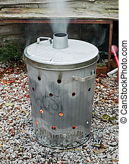 Garden incinerator bin burning garden waste with smoke coming out of the flue
