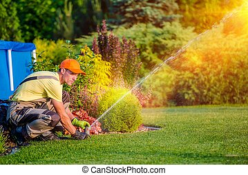 Garden Watering Systems. Garden Technician Testing Watering...