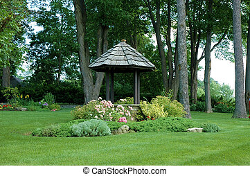 Pretty garden well / gazebo with bright green grass