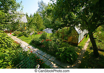 Garden with blossoming flowers, the house, hothouse and trees