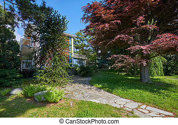 Garden with red beech tree and villa in a sunny summer day, Italy