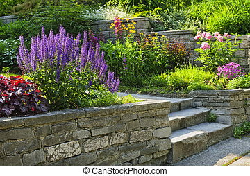 Natural stone landscaping in home garden with steps and flowerbeds