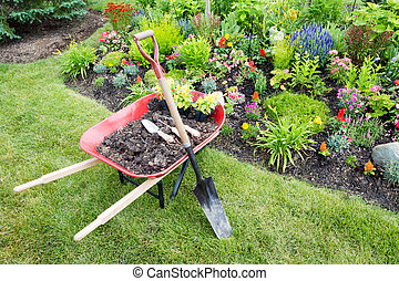 Garden work being done landscaping a flowerbed with a red...