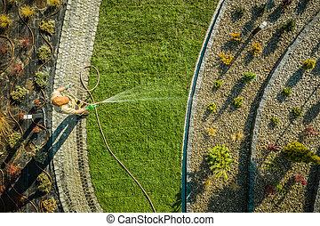 Garden Worker Watering Newly Installed Natural Grass