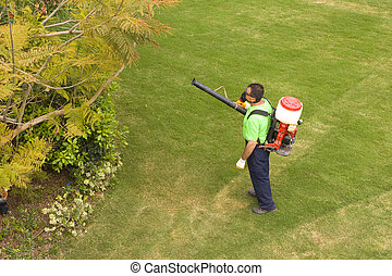 Gardener - A gardener is Spraying the trees