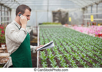 Gardener calling and taking notes in greenhouse