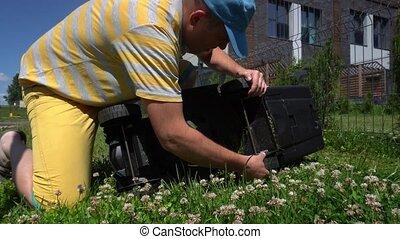 Gardener changing high of lawn mower blades. Gimbal motion...