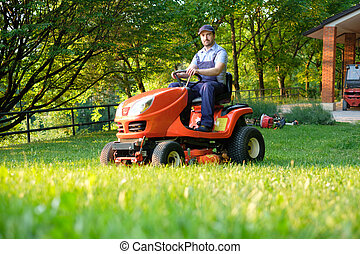 Gardener driving a riding lawn mower in garden