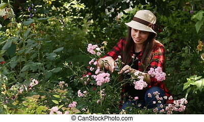 gardener girl trimming flowers with secateurs
