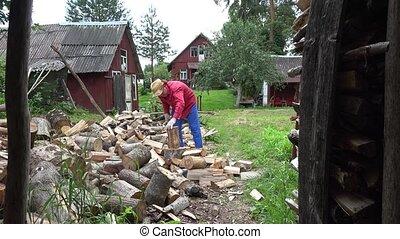 Gardener guy preparing natural wood fuel and rural houses. 4K