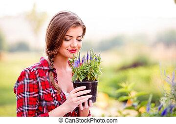 Gardener holding a seedling in flower pot, smelling it