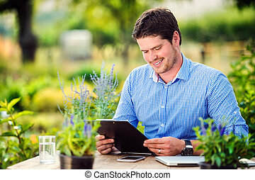 Gardener holding clipboard, at the table, green sunny natur