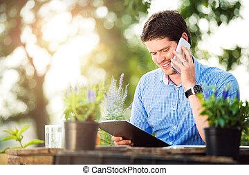 Gardener holding clipboard, making phone call, green sunny natur