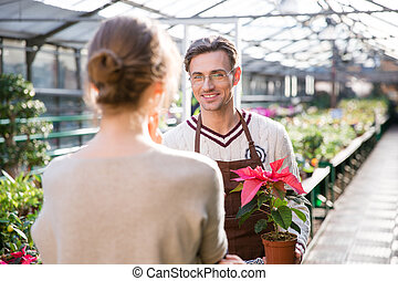 Gardener holding plant in pot and talking to young woman