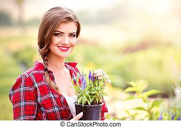 Gardener holding seedling in flower pot, green sunny nature