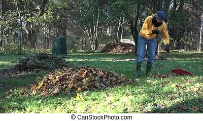 Gardener in warm clothes prepare autumn leaves form compost in backyard.