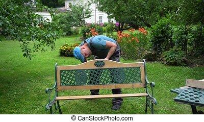 Gardener man disassemble retro bench in garden yard. Outdoor...