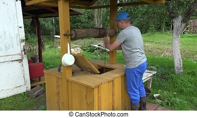 Gardener man guy draw water from well house and close wooden...