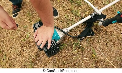 Gardener man hand starting gas lawn trimmer. Hands of a...