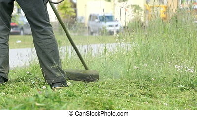 Gardener man mows grass to make beautiful design