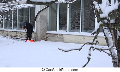 Gardener man shoveling snow from window sill and footpath...