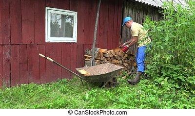 Gardener man unload firewood from wheelbarrow near wooden house. 4K