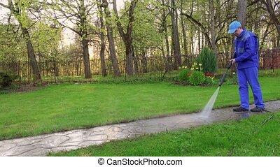 Gardener man wash footpath with high pressure water jet.