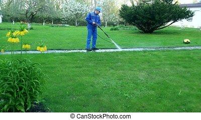 Gardener man washing footpath with high pressure water jet.