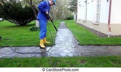 Gardener man washing stone path near his house in rural district.