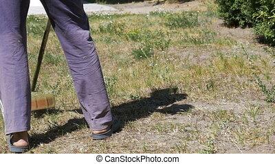 Gardener Mows Grass using a Portable Lawnmower