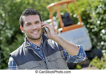 Gardener on telephone, digger in background