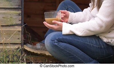 Gardener relaxes in rustic shed with mug of coffee medium shot